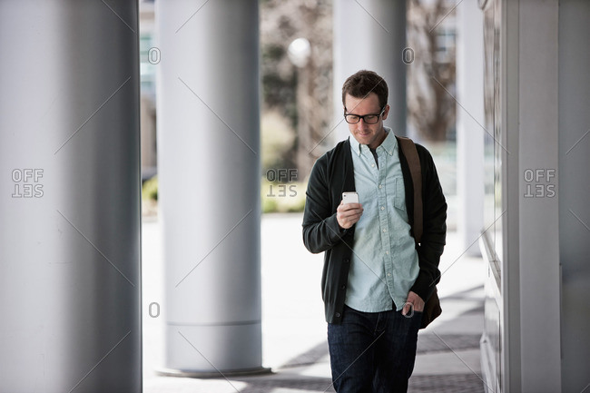 A man in casual clothes standing outside a building, checking his smart phone