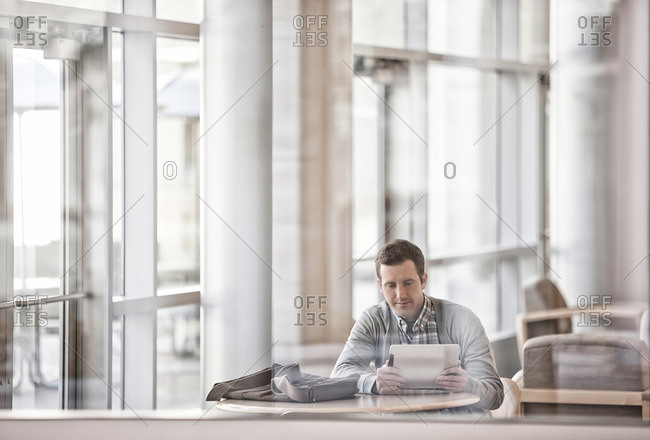 A man sitting in an open plan office by windows looking at a laptop