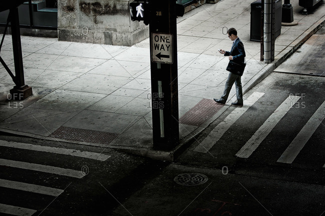 A man walking across a street crossing, looking at a phone in his hand