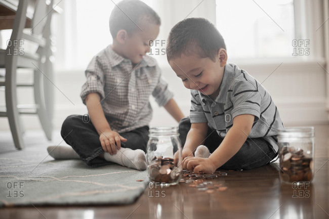 Two children playing with coins, dropping them into glass jars