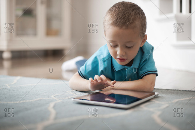 A young child lying on floor using a digital tablet with a touchscreen