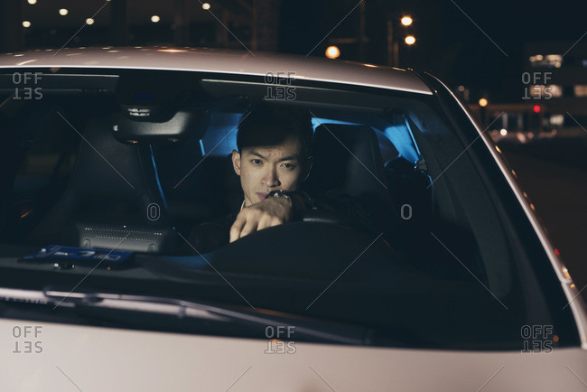 Young Asian man in a car at night