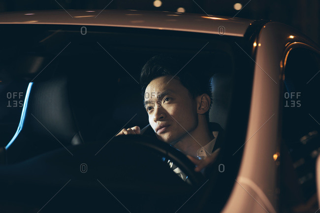 Young Asian businessman in a car with a cellphone at night