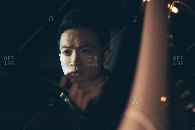 Asian businessman in a car at night