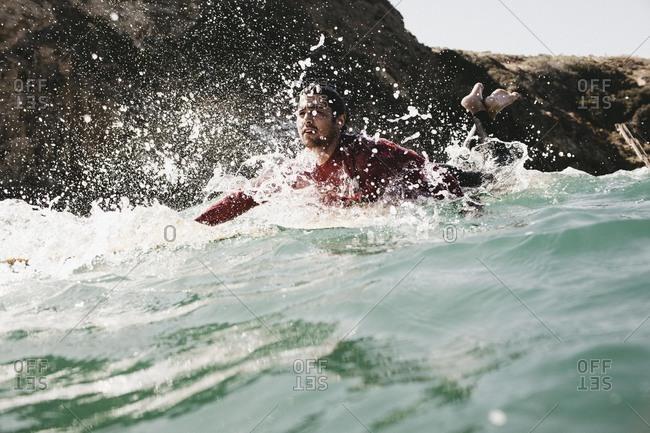 Men paddling through splashing ocean