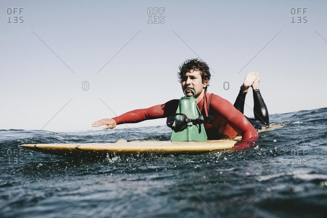 Man on surfboard with flippers in mouth