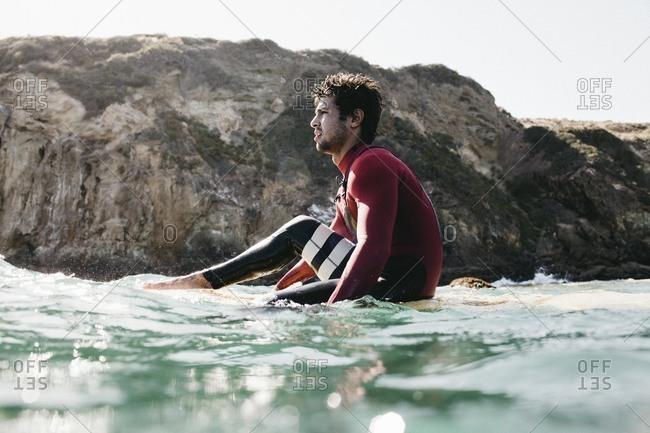 Man sitting upright on surfboard