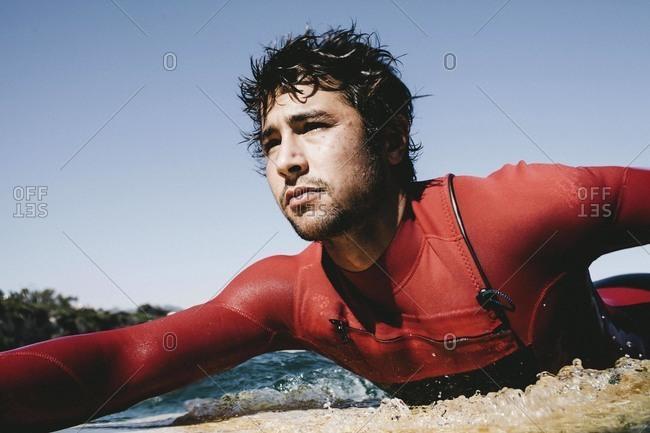 Portrait of man paddling surfboard