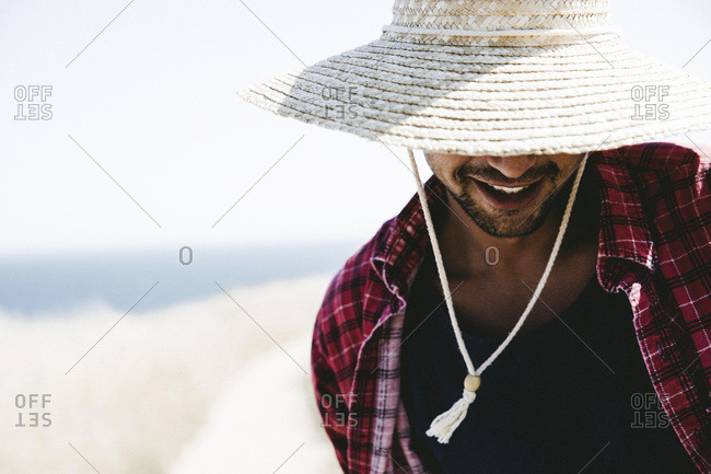Young man on beach in straw hat