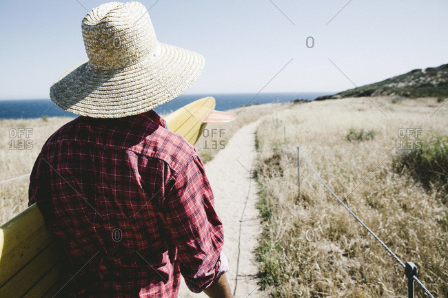 Man in straw hat with surfboard