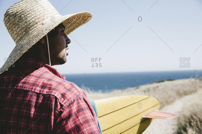 Man in straw hat with a surfboard