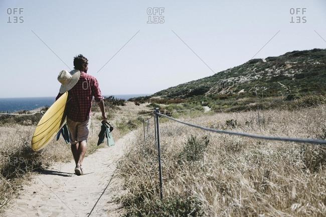 Man with surfboard on coastal path