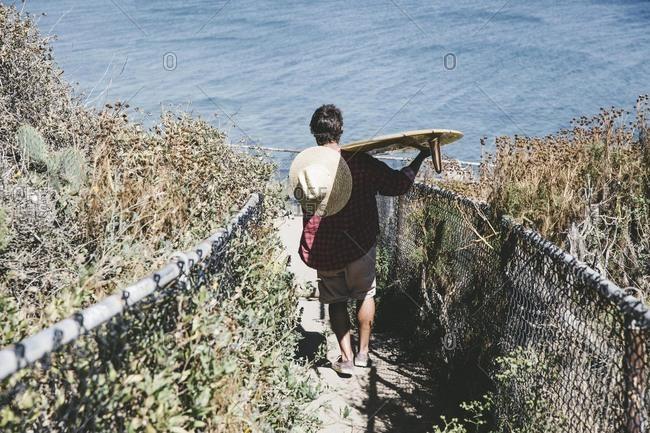 Man carrying surfboard down beach steps