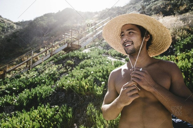 Young man in straw hat on beach