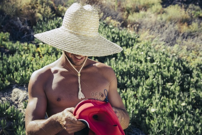 Man in straw hat holding wetsuit