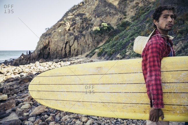Man in casual clothes with a surfboard