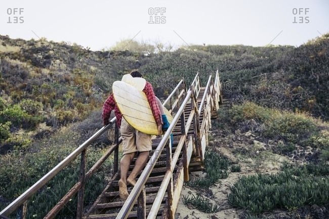 Man climbing up steps with surfboard