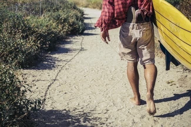 Barefoot man carrying surfboard