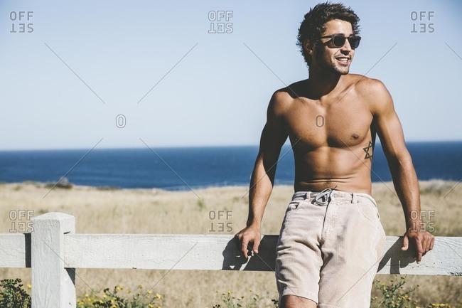 Shirtless man sitting on beach fence