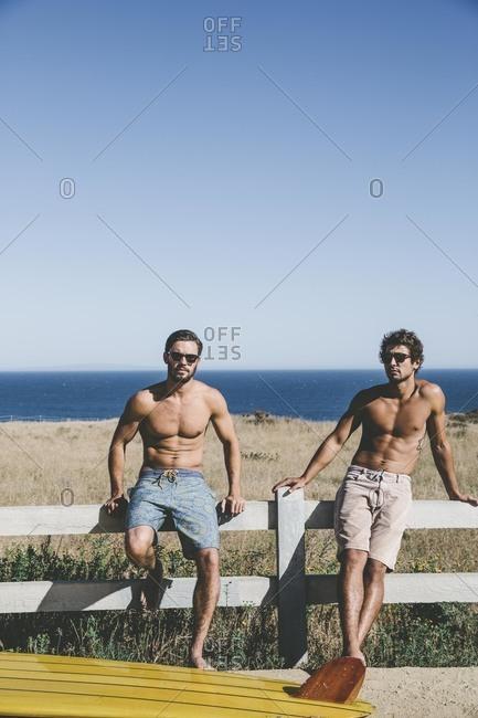 Shirtless men on beach fence