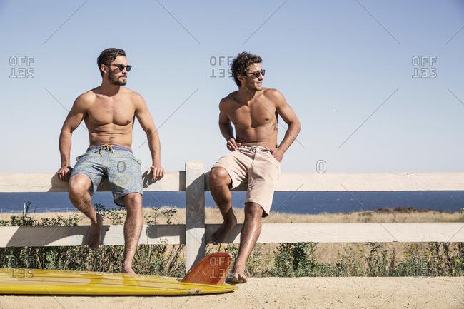 Shirtless men on a beach fence
