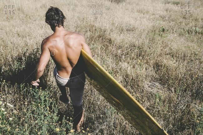 Man carrying surfboard through grass