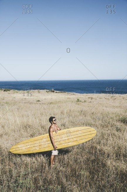 Man on grassy beach with surfboard