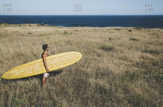 Man on a grassy beach with surfboard