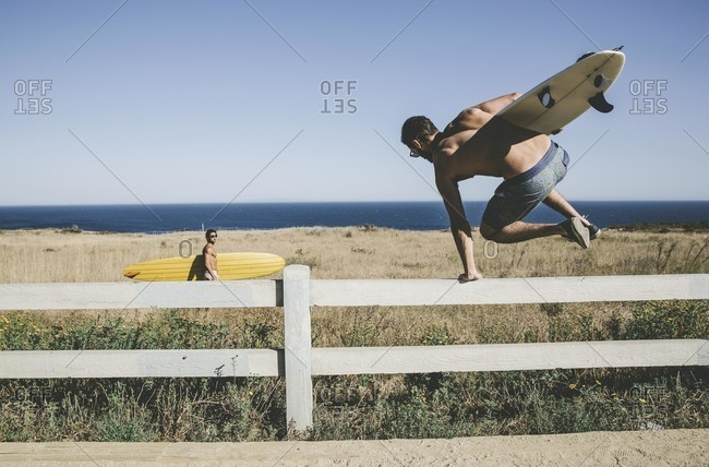 Men with surfboards jumping fence