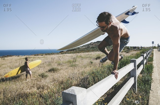 Men with surfboards jumping a fence