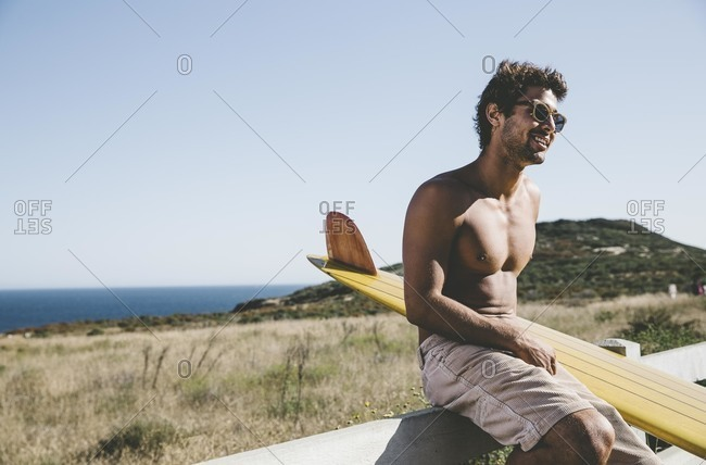 Man on fence by a surfboard