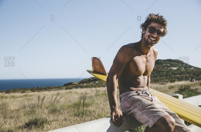 Man on fence with a surfboard