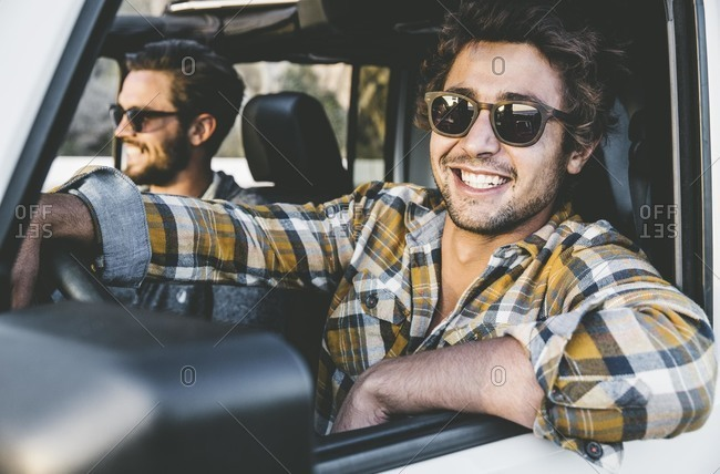 Smiling men looking out of SUV