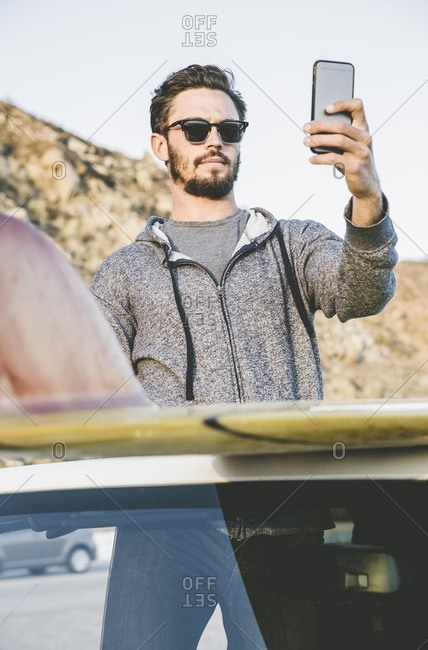 Man taking a beach picture from SUV