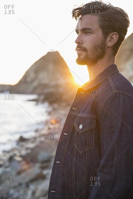 Man in jean jacket on beach