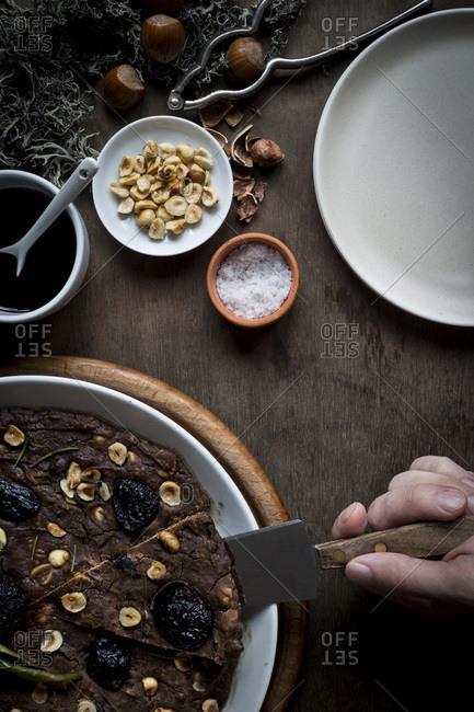 Person cutting of a festive Mediterranean Chestnut Flour Cake
