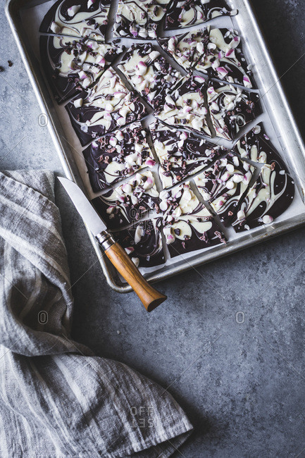 All-natural dark chocolate peppermint bark with cacao nibs and flaky salt on a baking dish