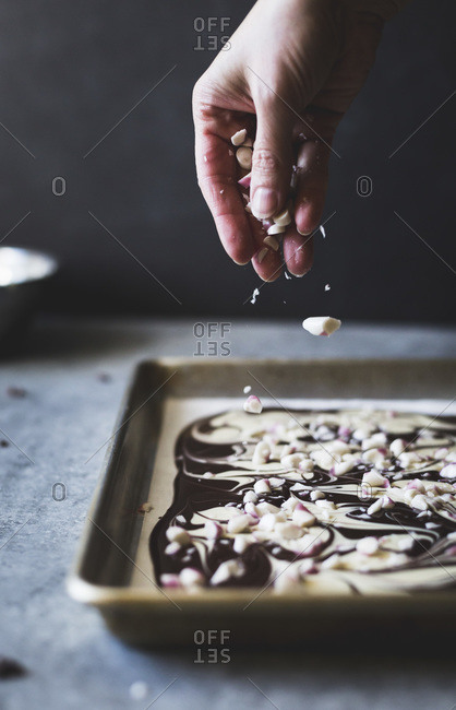 Person sprinkling peppermint onto baking pan with all-natural dark chocolate