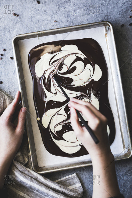 Hand swirling melted white and dark chocolate