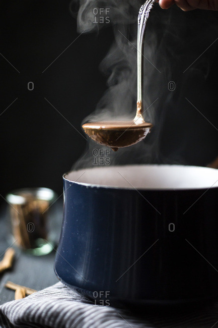 Person lifting spoon of dairy-free version of champurrado out of a saucepan