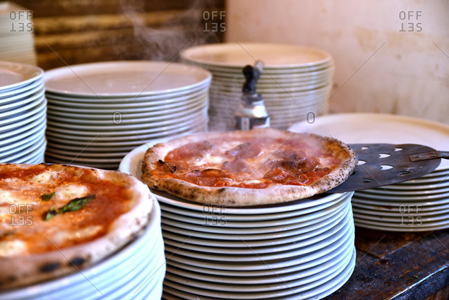 Pizzas being placed onto plates fresh out of the oven