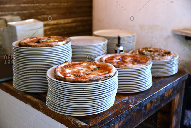 Plates stacked with pizzas on top