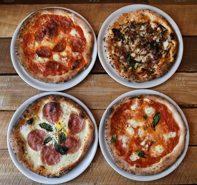 Four freshly baked pizzas