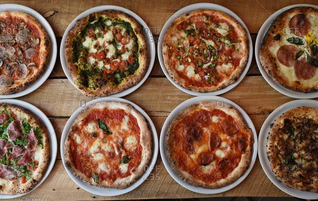 Eight freshly baked pizzas