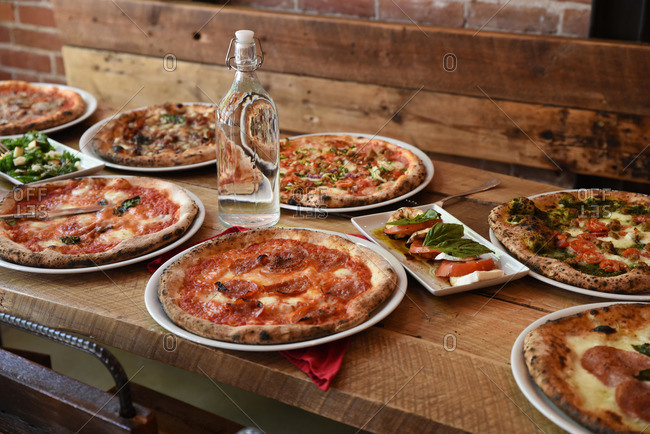 Pizzas and hors d'oeuvres on a table at a restaurant