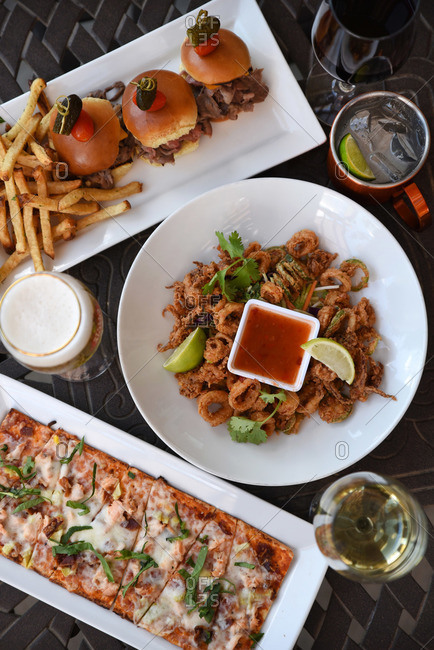 Pizza, sliders, and calamari hors d'oeuvres served on a table