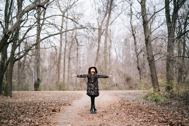 Girl with arms raised on wooded path