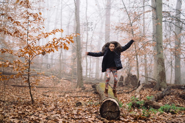Girl balancing on log in misty woods
