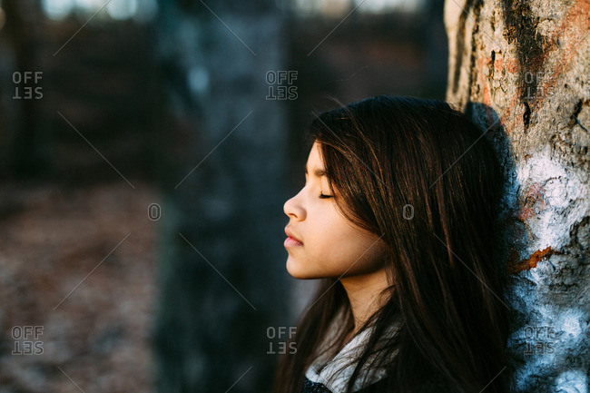 Girl leaning against tree with eyes closes