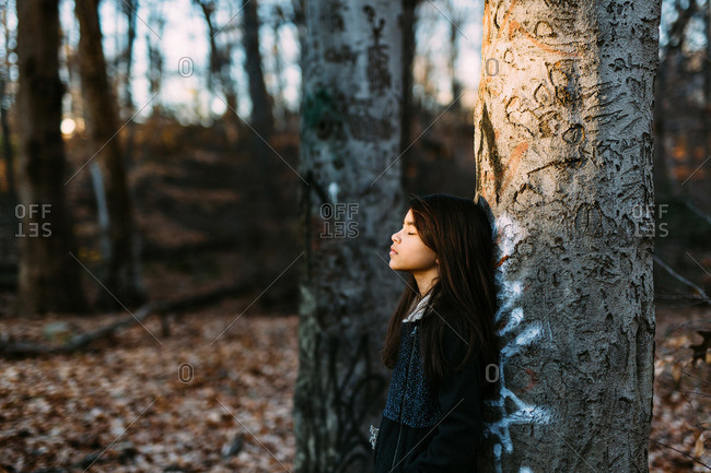 Girl resting against tree in woods